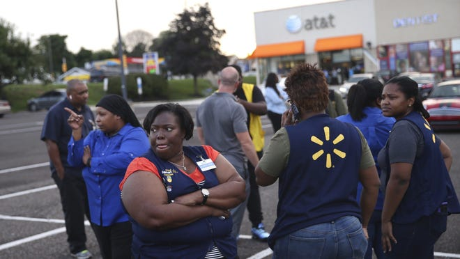 Walmart employees gather in the parking lot after a reported shooting at a Walmart in Wyncote, Pa., Tuesday, Aug. 14, 2018. Authorities say at least a few people were arrested after the reported shooting at the Walmart near Philadelphia. (Tim Tai/The Philadelphia Inquirer via AP)