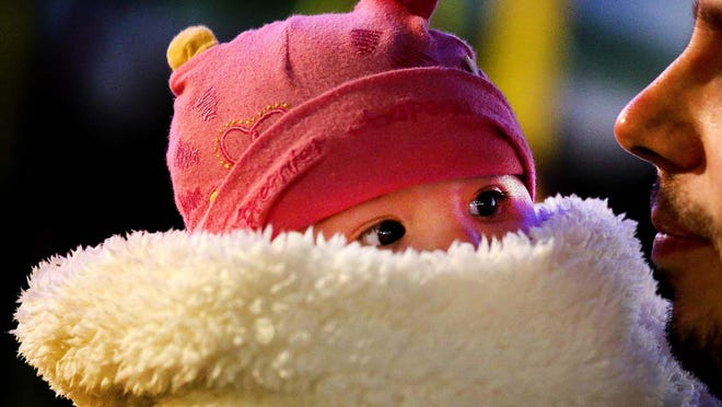 A four-month-old is snug as a bug during a cold snap at the South Florida Fair in 2014. As the fair opens Friday, fair-goers can expect some rain before a cool front hits South Florida.