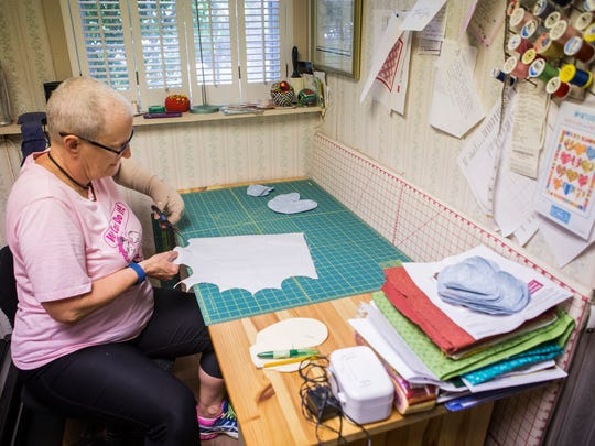 Eve English cuts out fabric hearts for quilts at her home in Newark on Thursday afternoon.