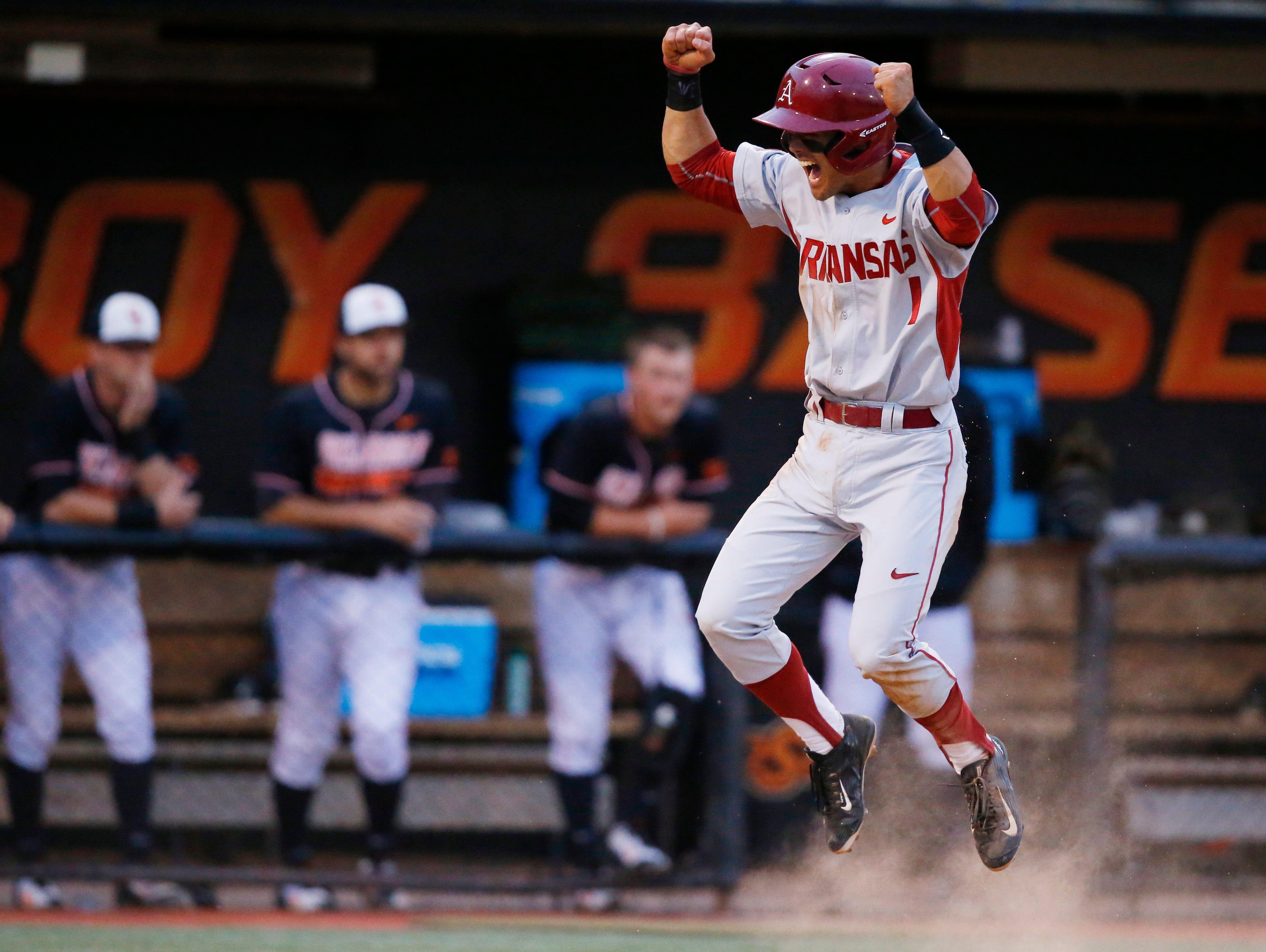 Arkansas' Rick Nomura celebrates after scoring in the eighth inning of an NCAA college baseball tournament regional game against Oklahoma State in Stillwater, Okla., Saturday, May 30, 2015. Arkansas won 7-5. (AP Photo/Sue Ogrocki)