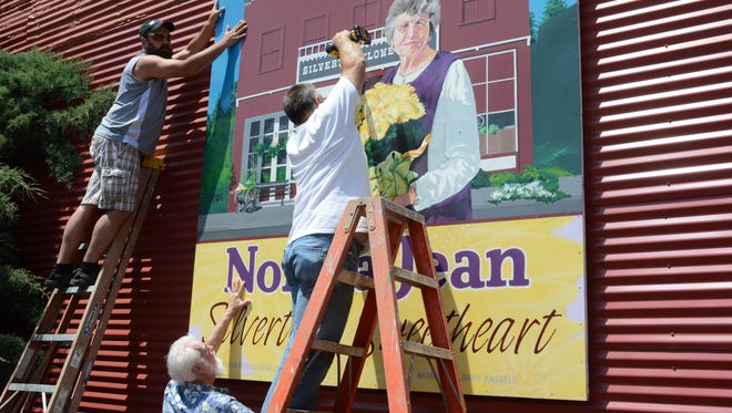 """Volunteers place a 8-foot-by-8-foot mural by artist Larry Kassell to honor Norma Jean Branstetter of Silverton on Wedensday, June 4, 2014.  Vince Till, immediate past president of the Silverton Mural Society, said the mural of Norma Jean is appropriate.   The privately funded mural is not a part of the society's holdings, but Till and his wife, Babs, spearheaded the funding efforts.  Babs Till said, """"Norma Jean has done so much for people without them knowing it ? without much fanfare.""""  A mural dedication will take place on June 22."""