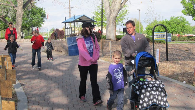 Colette Cox and Matthew Cox, along with their sons Eric Cox, left, and Evan Cox,  walk for the Cortez Fighters team at the 2015 Great Strides Walk for cystic fibrosis in Berg Park in Farmington.