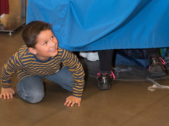 Jake Garcia, 6, crawls out under the dressing room curtain all smiles as he shows his personal shoppers his new shirt at the Dress the Child program Sunday evening at the Old Navy Store on Lohman Ave.