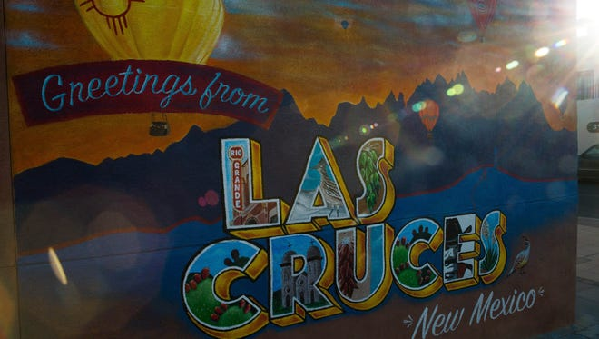 """Artists have created a """"Greetings from Las Cruces, New Mexico"""" mural on the north-facing wall of Insta-Copy, 318 N Main St. Seen here Wednesday Dec. 13, 2017, the mural was expected to be completed over the weekend. The mural was paid for with a grant through the New Mexico Resiliency Alliance."""