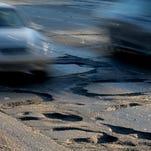 Cars navigate potholes in Southfield.