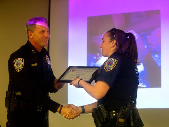 Police Chief Stan Standridge presents a life saving award to officer Katie Snell for keeping a stabbing victim from bleeding out last year.