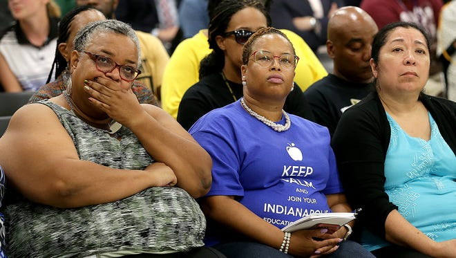 Rhondalyn Cornett, front row left, listens to IPS board members while the board prepares to vote to close three high schools Sept. 18, 2017.