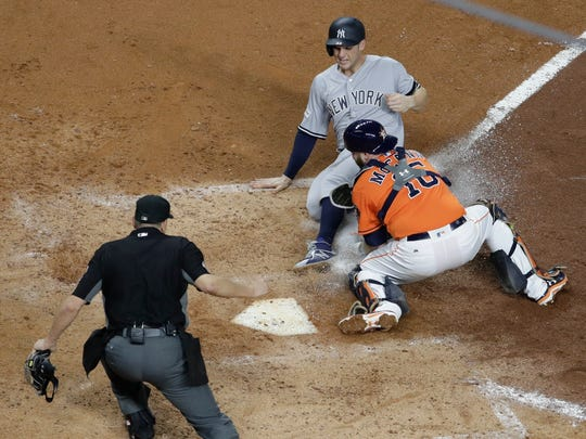Houston Astros catcher Brian McCann tags out New York Yankees' Greg Bird at home during the fifth inning of Game 1 of baseball's American League Championship Series Friday, Oct. 13, 2017, in Houston.