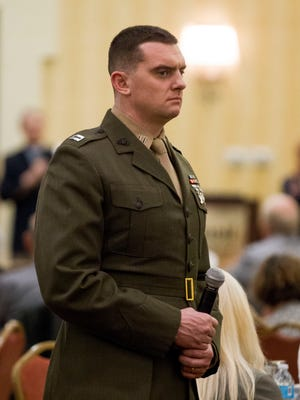 USMC Capt. James Prial holds a microphone for audience questions during an information session to update the families of prisoners of war and soldiers missing in action of the efforts that the U.S. Department of Defense is making to locate their loved ones at the Phoenix Marriott Mesa on Saturday, Jan. 28, 2017.