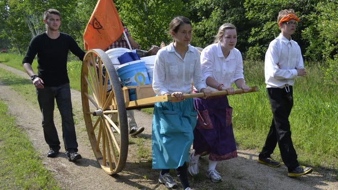 """Kiahna Johnson, second from left, and Courtney Brown, second from right, push an authentic wooden handcart with belongings stored on the back during the final mile of the """"Faith in Every Footstep"""" youth pioneer trek last week on Mountain-Bay Trail near Shawano. Accompanying Brown and Johnson, both of Shawano, are John Ficklin, left, of Algoma and Hawkins Batten, right, of Two Rivers."""