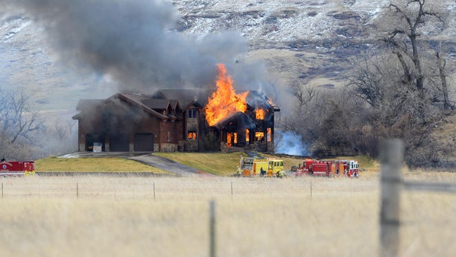The home at 55 Tumbleweed Lane is completely engulfed in flames Monday afternoon.