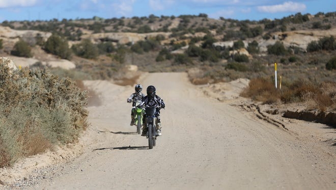 A pair of bikers ride near Chokecherry Canyon in Farmington on Tuesday. The trail was recently named the top four-wheeling trail in the state.