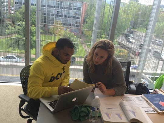 Oregon football player Charles Nelson (left) works with learning specialist Anna Poponyak in the Jaqua Center.