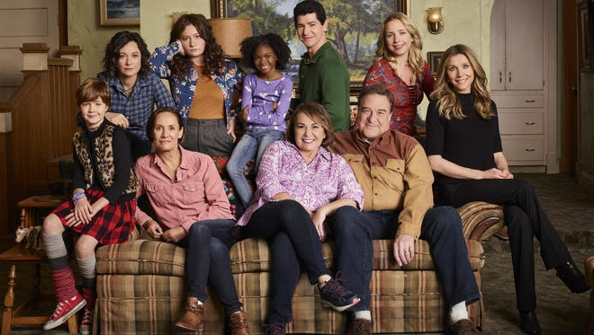 """The """"Roseanne"""" cast, on the couch from left: Ames McNamara as Mark, Laurie Metcalf as Jackie Harris, Roseanne Barr as Roseanne Conner, John Goodman as Dan Conner and Sarah Chalke as Andrea. Standing are Sara Gilbert, left, as Darlene Conner, Emma Kenney as Harris Conner, Jayden Rey as Mary, Michael Fishman as D.J. Conner and Lecy Goranson as Becky Conner. and Sarah Chalke as Andrea."""