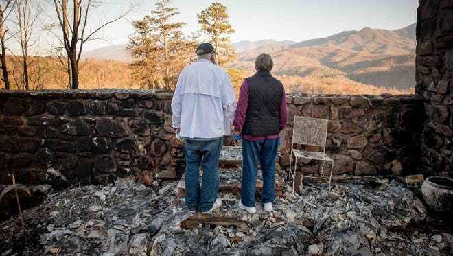 Richard T. Ramsey and Sue Ramsey hold hands while looking at the skyline from the remains of their house of 41 years, Thursday, Dec. 1, 2016, in Gatlinburg, Tenn. They safely evacuated from their home as fire approached Monday evening.