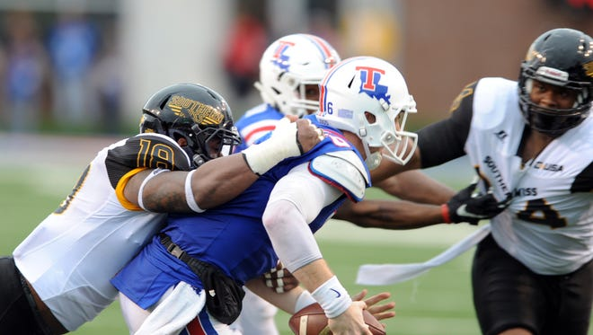 Southern Miss linebacker Brian Anderson tackles Louisiana Tech quarterback Jeff Driskel on Saturday during the Golden Eagles' game against the Bulldogs.