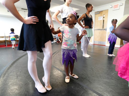 Zimora Palmer, 4, holds onto the hand of Addison Spey, with the Cary Ballet Company, during Plie All Day, an outreach program that hopes to bring dance to women's shelters throughout the Triangle. The program spent Thursday, April 20, 2017, at the women's shelter for the Durham Rescue Mission.