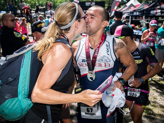 Michael Mendoza kisses his wife after completing Ironman 70.3 at the Prairie Creek Reservoir Saturday morning. Mendoza, who is a former Marine sniper and was critically injured by a grenade while serving overseas in 2006, has his sights set on beating the world record for completed half Ironmans in a year.