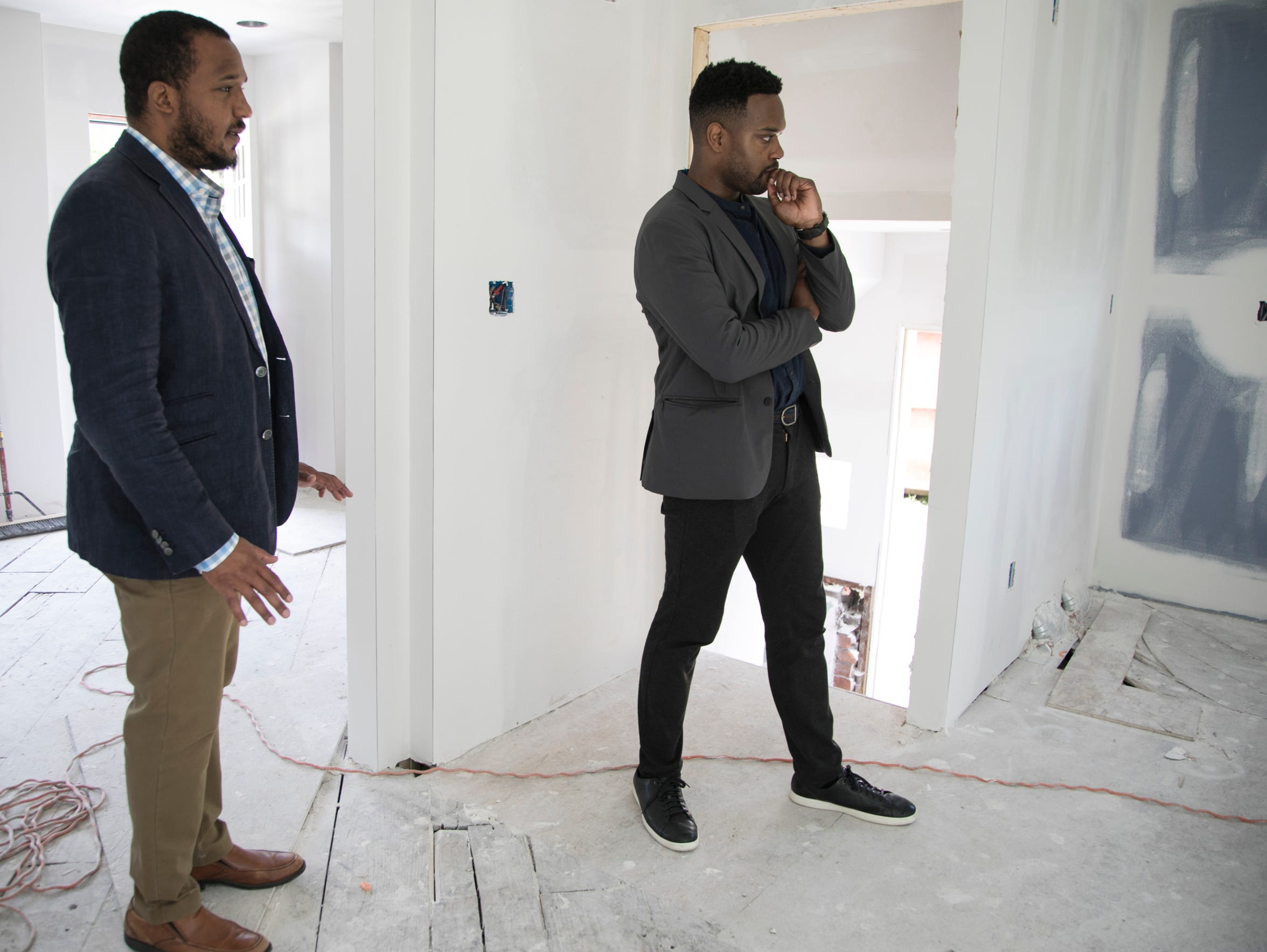 Century Partners co-founders Andrew Colom, left, and David Alade, check out one of the homes under construction in the Fitzgerald neighborhood in June on Lilac Street. The house will be the first home fully rehabbed as part of the revitalization project. Century Partners is supposed to rehab about 100 homes in the neighborhood by December 2020.