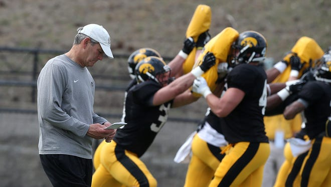 Iowa head coach Kirk Ferentz checks notes as members of his team run drills during last year's practice at Valley Stadium in West Des Moines.