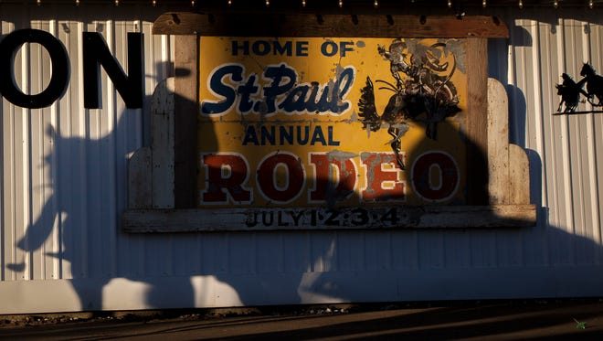 Riders cast shadows on the St. Paul Rodeo sign and arena as they make their way to the ring for the start of the annual St. Paul Rodeo, Tuesday July 3, 2018. The rodeo also serves as the annual fundraiser for many civic and community groups in St. Paul, Oregon.