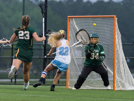 Cape Henlopen's Evelyn Shoop (22) gets the ball past St. Mark's Katharine Giannaras (34) to score one of her five goals in the DIAA Girls Lacrosse championship game at DE Turf Sports Complex in Frederica.