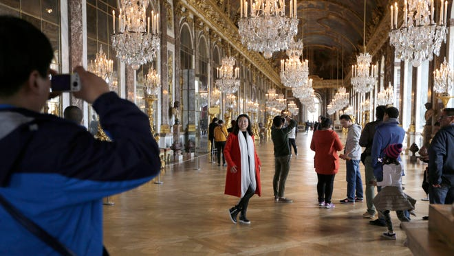 FILE - In this Nov. 17, 2015, file photo, visitors pose inside the Hall of Mirrors in the Versailles castle in Versailles, west of Paris. Rick Steves' summer travel tips include getting tickets in advance for major attractions so you can skip the line and avoid the crowds, and following local cultural customs to beat the heat, such as taking an afternoon siesta or dining late in the evening when it's cooler. (AP Photo/Amr Nabil, File)