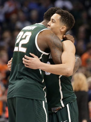 Michigan State's Branden Dawson, left, hugs Travis Trice, right, at the end of an NCAA tournament college basketball game against Virginia on March 22, 2015. Both have been trying out for NBA teams.