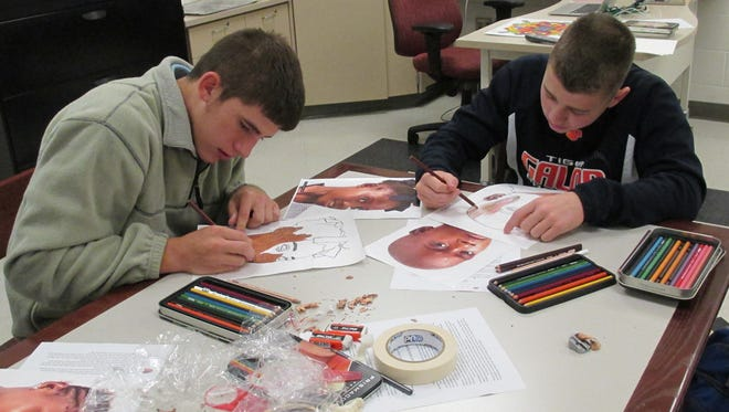 Galion High School art students Austen Strickler (left) and Colten Cox (right) work on a special project for vulnerable children as part of The Memory Project.