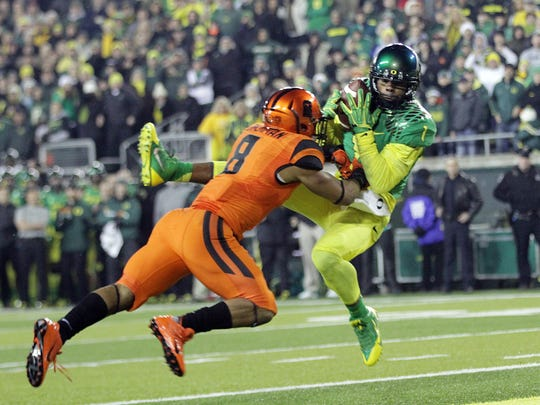 Josh Huff catches the game-winning touchdown with less than a minute left as Oregon defeats Oregon State 36-35 in the annual college football battle for state bragging rights, the Civil War.