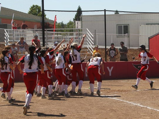 Simpson University's softball team congratulates Jessica Dager after she hit a home run in their win over Oregon Tech at an NAIA Regional. The Red Hawks would go on to play in the NAIA softball World Series.