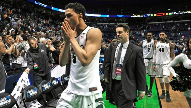MSU's Bryn Forbes covers his mouth when walking off the floor with shocked Spartans.