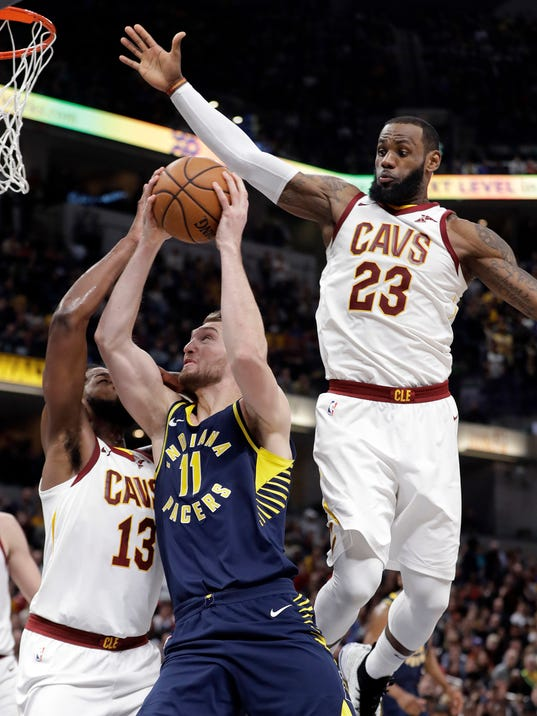 Indiana Pacers' Domantas Sabonis (11) shoots against Cleveland Cavaliers' Tristan Thompson (13) and LeBron James (23) during the second half of an NBA basketball game, Friday, Jan. 12, 2018, in Indianapolis. (AP Photo/Darron Cummings)