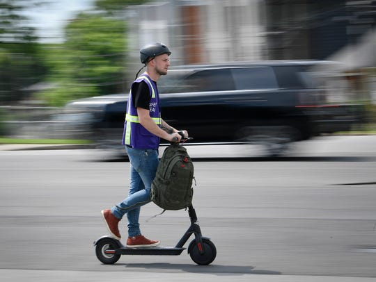 A rider speeds along 12th Ave. South atop a Bird scooter