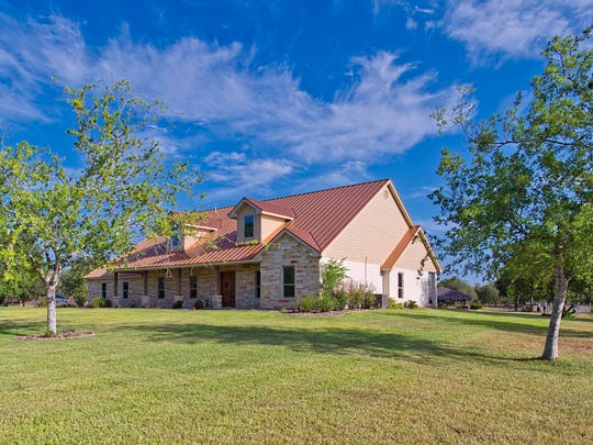 5601 Killarney Close, Mathis sits on 20 tree shaded acres near Old San Patricio.   The stone home has a copper metal roof , a separate guest home, a pond and swimming pool.