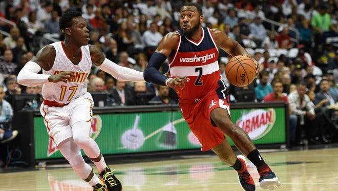 Washington Wizards guard John Wall (2) dribbles past Atlanta Hawks guard Dennis Schroder (17) during the first half at Philips Arena.