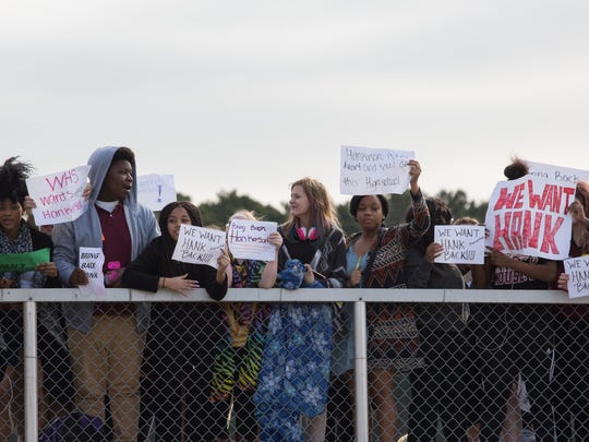 Students from Washington High School stand in protest of the recent termination of Principal Sidney Hankerson in the bleachers of Washington High School's athletic field on Friday, March 11, 2016.