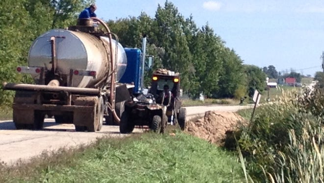 Contractors transfer spilled manure into waiting trucks along County D in the Door County town of Brussels.