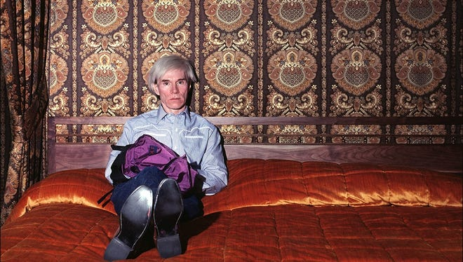 Andy Warhol sits on his bed at the Best Western University Inn, where he stayed during a visit to Fort Collins in September 1981.