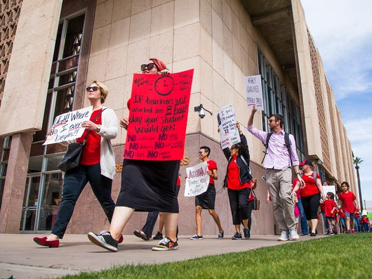 Teachers hold up signs at the #RedForEd rally at the Arizona state Capitol protesting low pay March 21, 2018.
