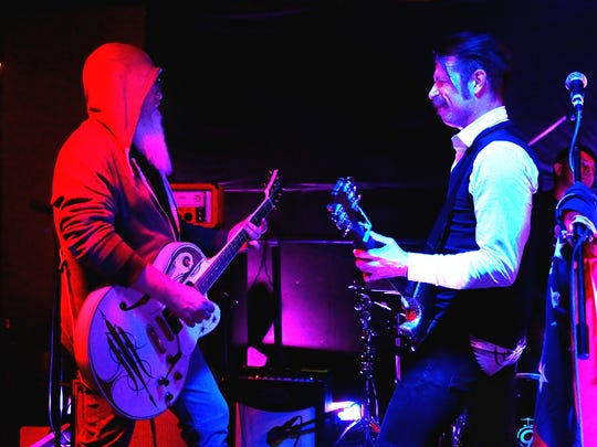 Dave Catching (left) and Jesse Hughes of Eagles of Death Metal duel Saturday, Jan. 18, 2014 at Schmidy's Tavern in Palm Desert.  On Friday, Nov. 13, 2015, Eagles of Death Metal was performing in Paris when hostages were taken and killed during their concert.