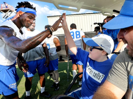 MTSU's Jeremy Cutrer (8) gives a high-five to Colton Sheets a young cancer survivor as he tours practice on Thursday, Sept. 22, 2016. Colton will be MTSU's honorary Captain for the home game against Louisiana Tech, this Saturday.