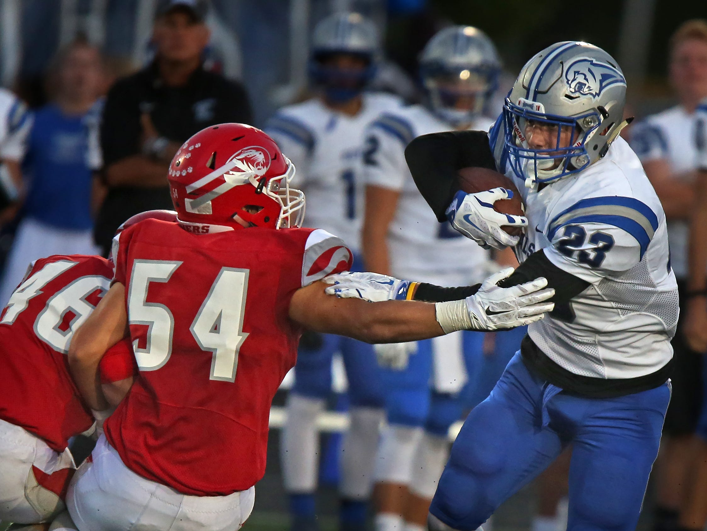 Fishers' #54 Trent Nielson reaches to try to stop Hamilton Southeastern's #23 Aaron Matio during first half action of the Hamilton Southeastern at Fishers football game, Friday, September 11, 2015.