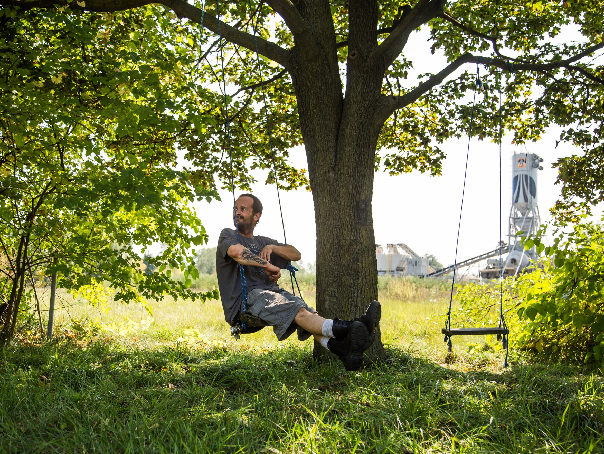 George Chene, 39, of Detroit sits on a swing he found