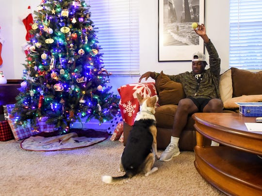 JaJuan Cherry of Okeechobee plays fetch with one of the family dogs, Roxie, Friday, Dec. 1, 2017, at his home in Okeechobee.