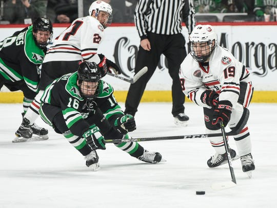 Grant Mismash of North Dakota and Mikey Eyssimont of St. Cloud State try to control the puck near center ice during the third period of the NCHC Frozen Faceoff Friday, March 16, at the Xcel Energy Center in St. Paul.