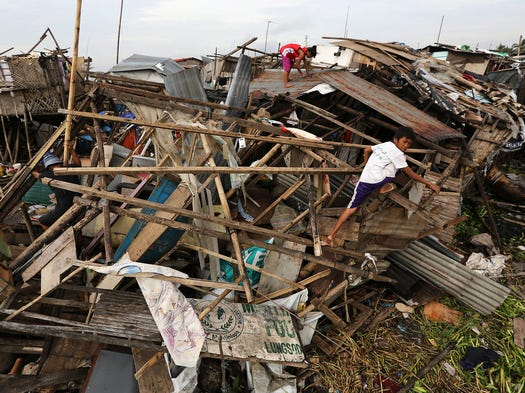 People search among homes destroyed by Typhoon Rammasun on July 17 in Muntinlupa, Philippines. Thirty-eight people were killed by the storm.