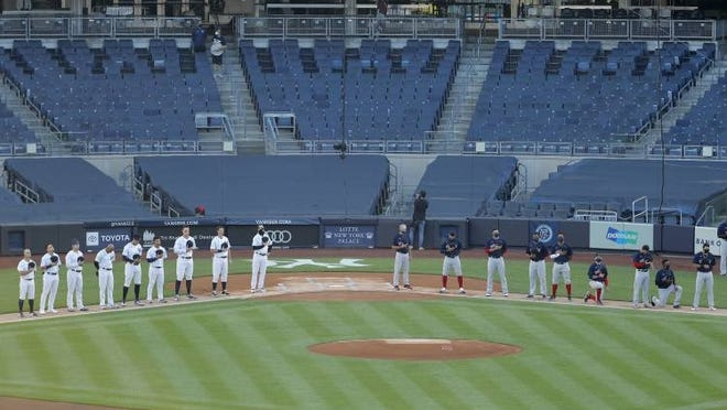 The New York Yankees, left, and Boston Red Sox line up for the national anthem before the baseball game Friday night at Yankee Stadium.