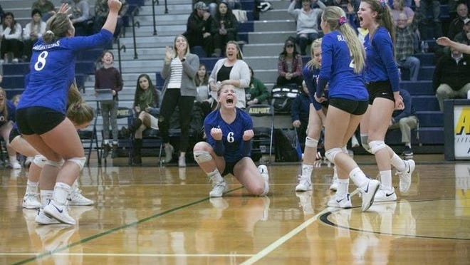 Ida's volleyball team celebrates after winning a point last season with Ashley Begeman (white sweater) in the background. Begeman was hired Monday night to take over as varsity coach this season.