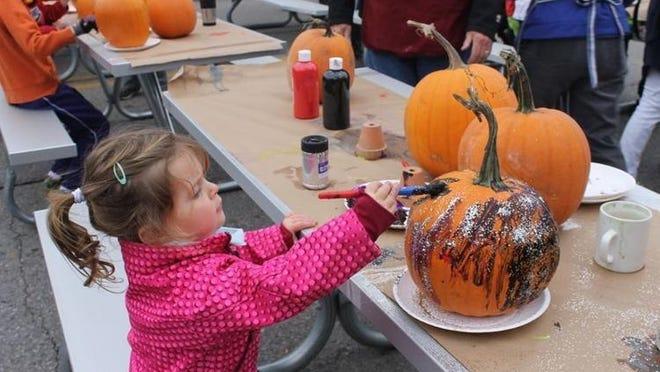 Ellie Manthei paints a pumpkin, during a previous Boyne City Harvest Festival, in downtownBoyne City.